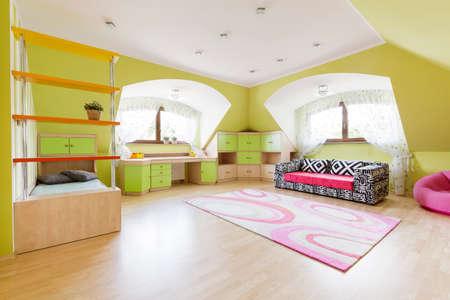 Ruime kinderkamer met luxe sofa bij de muur en roze tapijt op een houten parket