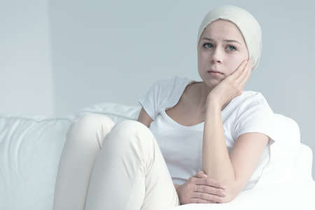 Woman with cancer sitting on a couch resting her hand against her cheek