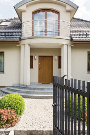 Elegant entrance tot he big expensive villa with balcony. Open gate leading through the pavement to the wooden door Zdjęcie Seryjne