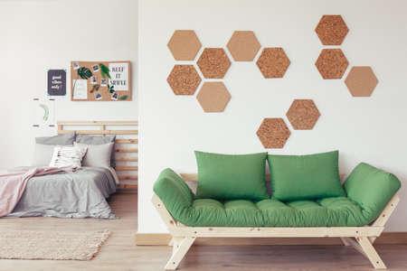 Divano verde con cornice in legno naturale in interni minimalisti e accoglienti con camera da letto aperta Archivio Fotografico - 83595825