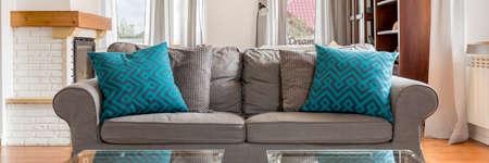 居心地の良いグレーのソファーにパターンのターコイズの装飾的な枕