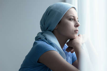 Breast cancer survivor in a blue scarf resting chin on her hands