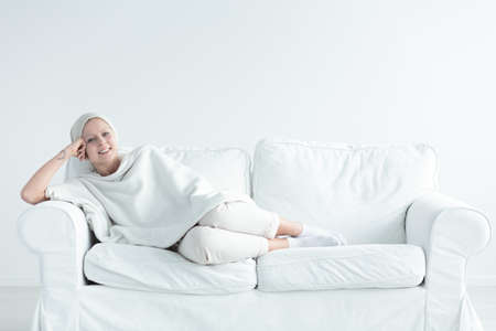 Breast cancer survivor lying on a couch smiling happily. Stock Photo