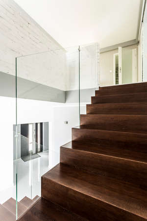 Modern staircase with transparent banister and wooden steps