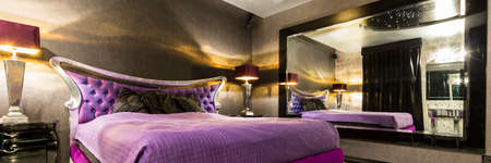 Glamour bedroom with purple, marital bed, elegant lamps and a mirror