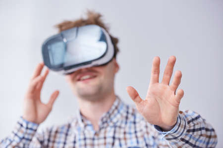 Male immersed in virtual reality video game doing gestures while using VR glasses