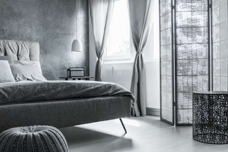 Simple comfortable bedroom with gray wall, soft linens and screen divider