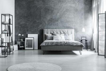 モダンなベッドルームに、シンプルな家具、灰色のベッド、ヘッドボードが柔らかい