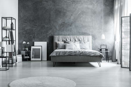 Modern bedroom with simple furniture, gray bedding and soft headboard