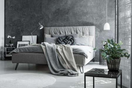 Współczesna sypialnia z skandynawskim szarym dekorem, rośliną i ręcznie robioną poduszką