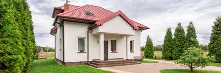 列と赤い屋根の小さな白い住宅