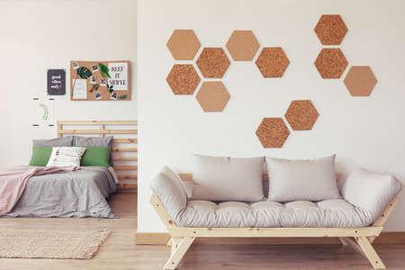 Modern natuurlijk slaapkamerontwerp met pastelkleuren, eenvoudig houten meubilair, witte muur en ecodecor Stockfoto