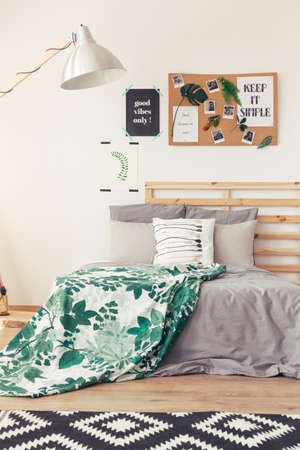 grey rug: Close-up view of bedroom in natural design with white wall, lamp, posters, photos, rug, wooden floor and bed with gray and botanic bedding