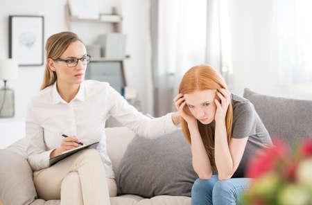 精神科医のセッション中にフォームの神経衰弱に苦しんで不幸な少女