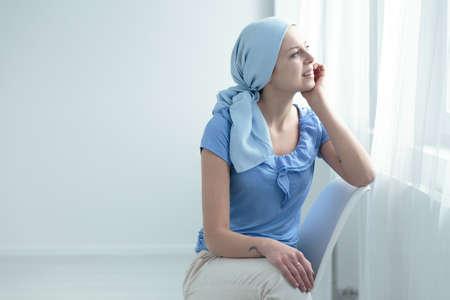 Brustkrebs-Überlebender, der auf einem weißen Stuhl sitzt und glücklich das Fenster schaut Standard-Bild - 83654125