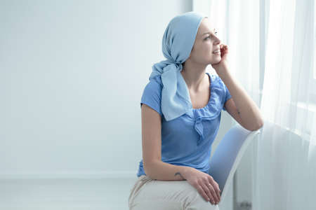Sopravvissuto al cancro al seno seduto su una sedia bianca, felicemente guardando fuori dalla finestra Archivio Fotografico - 83654125