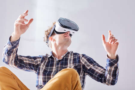 Young guy sits with crossed legs and moves to future with VR glasses Stock Photo