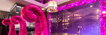 Dining area in glamour style with purple wall, backlight and the chandelier