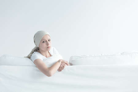 Sick girl leaning on white sofa with a longing look in her eyes Reklamní fotografie - 83654170