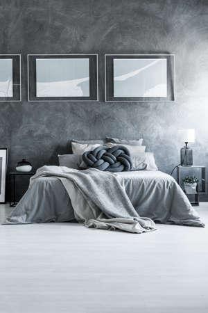 灰色の綿の寝具、枕カバー キングサイズ ベッドの居心地の良いアパートメントで