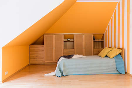 Cozy small bedroom designed in a minimalistic and modest style at the attic. Big thick mattress as a bed next to wooden shelves Imagens