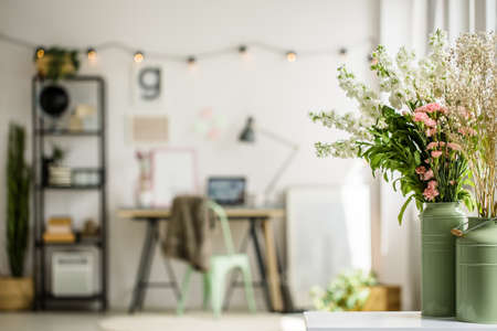home office interior: Wildflowers in two green milk jugs on white shelf in scandi style room Stock Photo