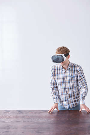 Boy relies on a wooden table when playing in virtual reality using electronic glasses Stock Photo