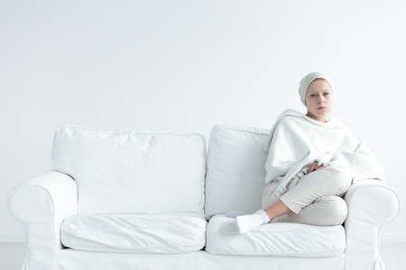 Girl with tumor covered with white blanket,sitting on a sofa,
