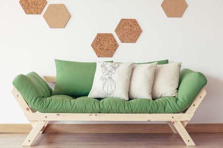 Trendy green sofa in perfect interior for a nature lover with beige pillows and wooden frame