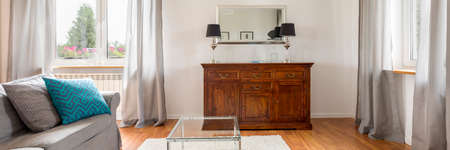 Elegant wooden commode in little bright living room Zdjęcie Seryjne
