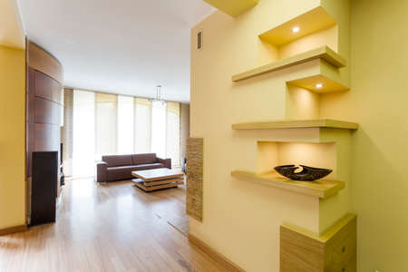 Big hallway with wooden parquet leading to living room. In the wall cut shelves cover with wood Stock Photo