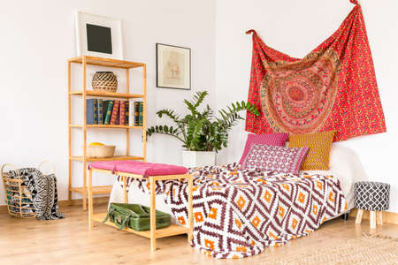 Cozy ethnic bedroom with wooden book-stand and oriental cloth