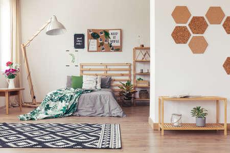 자연 장식, 회색 및 녹색 침구, 랙, 깔개, 꽃병, 꽃, 코르크 액세서리 및 목제 가구와 함께하는 에코 스타일 트렌디 룸