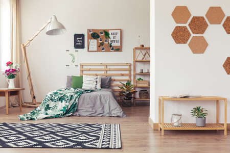 Trendy room in eco style with natural decor, gray and green bedding, rack, rug, vase, flowers, cork accessories and wooden furniture