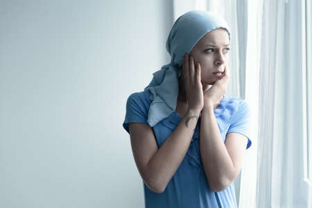 Patient with cancer looking out the window while worrying about the future