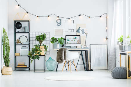 Grandi cactus su un vaso di fiori ecologico nella stanza bianca con la linea di lampadine sulla parete. Concetto di design per l'home office Archivio Fotografico - 83611237
