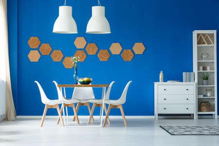 로얄 블루 벽과 심플한 가구로 강조된 개방적이고 넓은 식사 공간을 갖춘 모던 한 거실 스톡 콘텐츠