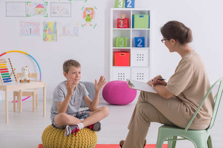 Child talking to therapist in colorful classroom with toys