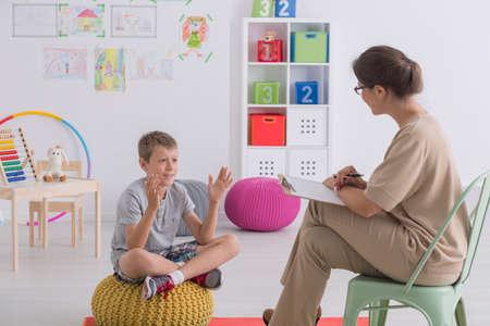 Kind praten met therapeut in kleurrijke klaslokaal met speelgoed