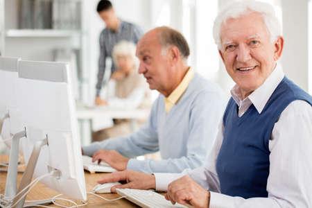Happy grandpa enjoying learning during computer classes for seniors