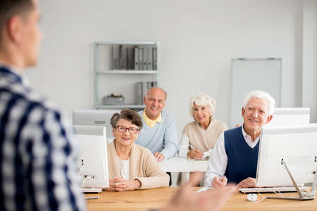 Old happy people listening to their teacher talking about technology