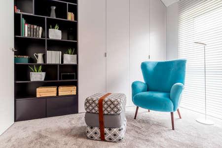 Intérieur moderne avec coin lecture confortable avec bibliothèque noire, fauteuil bleu, pouf et grande fenêtre avec stores Banque d'images - 83756099