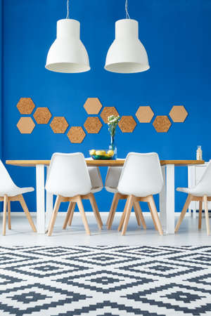 DIY honeycomb cork on blue wall in modern natural dining room with wooden communal table, white chairs and patterned rug