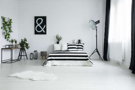 White fur on floor in minimalistic bedroom with two plants in striped material pots and glass box on table