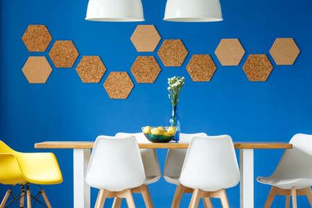Koningsblauwenmuur in eenvoudige Skandinavische eetkamer met houten en witte communale lijst, stoelen en honingraatcork muurdecor