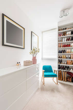Elegant white walk-in closet with shoes organized on shelves, window blinds, sideboard, blue armchair and pink pastel details Stock Photo
