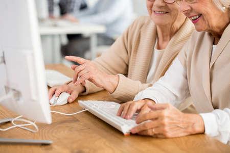 Foto del primo piano delle mani delle donne sulla tastiera e sul topo di computer bianchi