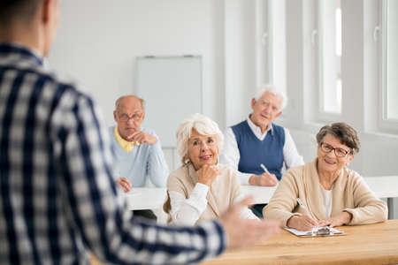 Anziani donne e uomini che fanno note dalle lezioni IT