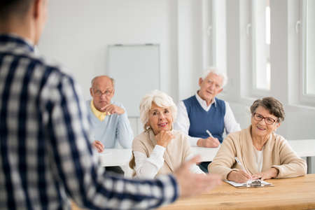 third age: Elder women and men making notes from IT lectures Stock Photo