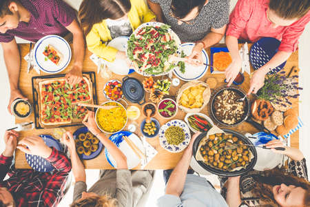 Vegetariërs delen gebakken aardappelen en gezonde salade samen tijdens een vegetarische lunch